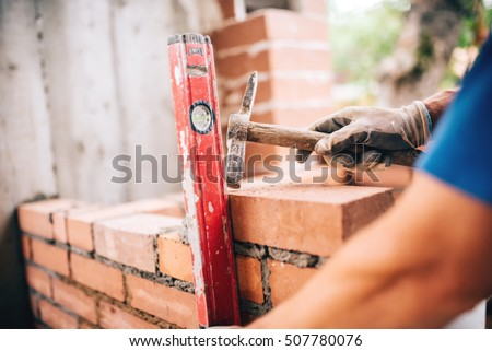 industrial worker building exterior walls, using hammer and level for laying bricks in cement. Detail of worker with tools