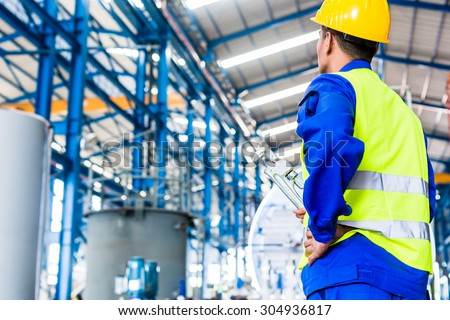 Industrial worker in Asian factory with tools going to machine maintenance