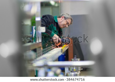 Industrial worker in manufacturing plant grinding steel structure. Sparks from grinding machine in workshop. Industrial background, industry.