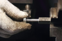 Industrial worker make a stud and bolt by lathe machine