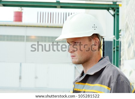Industrial Worker, serious looking, controls work in a factory