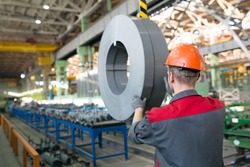 Industrial worker transporting transformer steel cargo with workshop rail mounted gantry overhead crane
