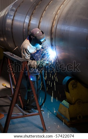 Industrial worker welding in factory