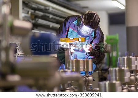 Industrial worker with protective mask welding inox elements in steel structures manufacture workshop. Stockfoto ©