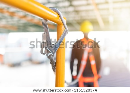 Industrial Worker with safety protective equipment loop hanging on the back and hand holding the rope, safety concept #1151328374