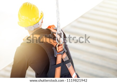 Industrial Worker with safety protective equipment loop hanging on the back sitting above the container, safety concept #1119821942