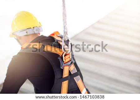 Industrial Worker with safety protective equipment loop hanging on the back sitting above the container, safety concept #1467103838