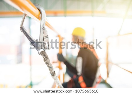 Industrial Worker with safety protective equipment loop hanging on the bar besides #1075663610