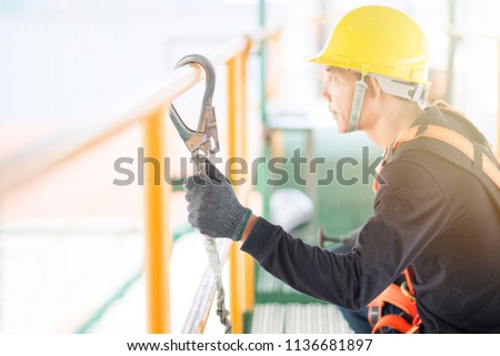Industrial Worker with safety protective equipment loop hanging on the bar besides #1136681897