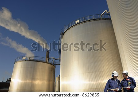industrial-workers in front of refinery oil storage tanks, smoke and blue-sky in background