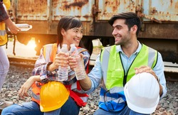 Industrial workers or Rail transport engineers in protective clothing are drinking water to quench their thirst beside the freight train after working hard during the day outdoors.