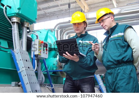 Industrial workers with notebook working in a power plant, teamwork