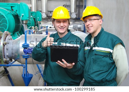 Industrial workers with notebook working in power plant, teamwork well done