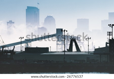 Industrial zone in the morning fog with the skyline in the background