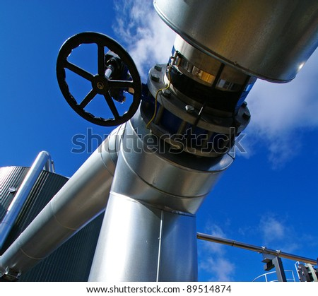 Industrial zone, Steel pipelines and tanks against blue sky