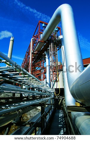 Industrial zone, Steel pipelines, smokestack and valves against blue sky