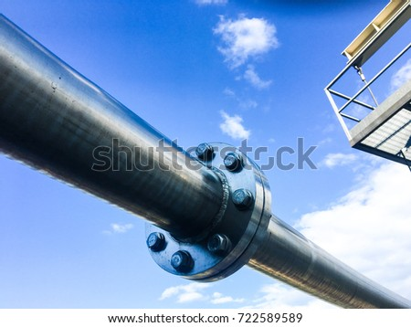 Industrial zone, Steel pipelines , valves and flange against blue sky #722589589