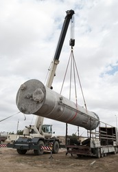 Industrial zone. Unloading of processing equipment by means of the crane