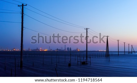 Industrial zone which is visible in the distance and the sea and the telephone poles #1194718564