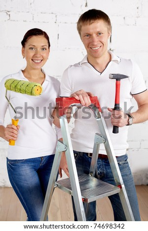 Industrious couple with paint roll and hammer looking at camera in new house
