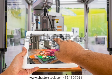 Industry 4.0 and Augmented reality for industry concept. Hand holding tablet with A/R manufacturing system control application on automate machine in smart manufacturing background.