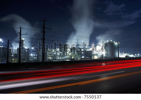 industry area with traffic and smoke stacks by night