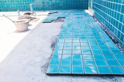 Industry building construction architecture worker professional man builder are installation blue swimming pool ceramic tiles on cement concrete floors and wall
