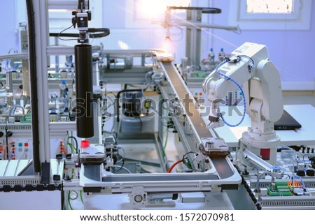 Industry 4.0 concept; artificial intelligence in smart factory prototype. Robot picks up the product from automated car on the manufacturing line. Focus on robotic arm's gripper. Selective focus.