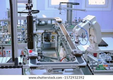 Industry 4.0 concept; artificial intelligence in smart factory prototype. Robot picks up the product from automated car on production line. Focus on robotic arm's gripper. Selective focus.