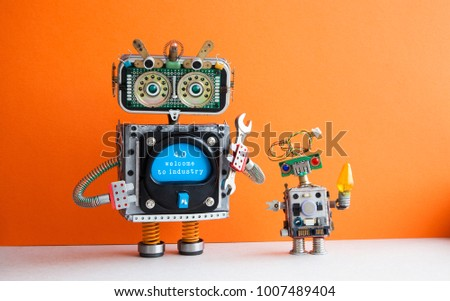 Industry 4.0 concept. Big IT specialist robot with hand wrench and small robotic cyborg. Welcome to the new economic future message on blue display. Orange wall background.