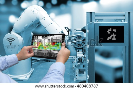Industry 4.0 concept .Man hand holding tablet with Augmented reality screen software and blue tone of automate wireless Robot arm in smart factory background #480408787