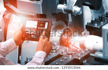 Industry 4.0 ,  concept  of Man hand holding cell phone or tablet with Augmented reality screen software and blue tone of automate wireless Robot arm in smart factory background. Mixed media