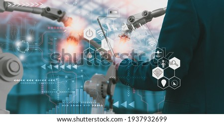 Industry engineer in factory,using smart tablet glass device,control automated robot arm machine learning operation,concept business and industry 4.0,Artificial intelligence or AI,with 5G network
