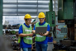 Industry engineer team worker teaching help talking production machine and setting it for work in modern factory. staff operate control heavy machine in factory