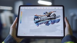 Industry 4.0 Factory: Chief Engineer and Project Supervisor Holds Digital Tablet Computer. Screen Shows 3D Concept of New Jet Engine. Workshop with Technologically Advanced Machinery.