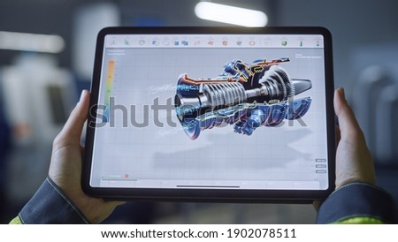 Industry 4.0 Factory: Chief Engineer and Project Supervisor Holds Digital Tablet Computer. Screen Shows 3D Concept of New Jet Engine. Workshop with Technologically Advanced Machinery. Foto stock ©