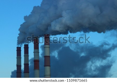 Industry, industry and ecology - gray-blue smoke from the red-white pipes of the plant (chemical plant power plant), thermal power plant against the blue clear sky #1109871665