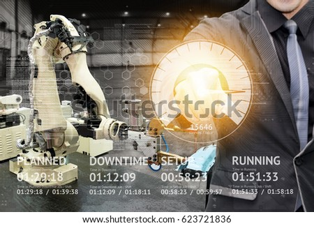 Industry 4.0 internet of things concept. Application UI screen and Man suit Engineer finger point to screen for control automation wireless robot machine arm background in smart factory.