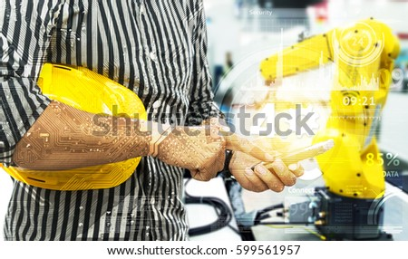 Industry 4.0 internet of things concept. Engineer finger point to smart phone for control blur robot machine arm background , yellow hat and industrial graphic in smart factory.