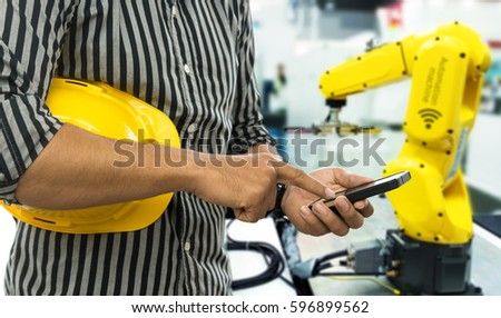 Industry 4.0 internet of things concept. Selective focus on Engineer finger point to smart phone for control blur robot machine arm background and yellow hat in smart factory.