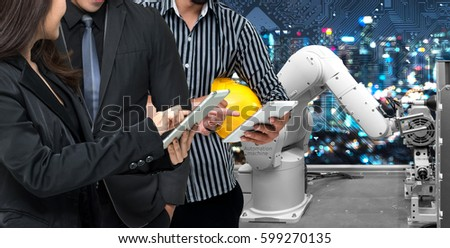 Industry 4.0 internet of things concept.Two Business man and woman suit.One Engineer using tablets for monitoring automation wireless robot machine arm in smart factory with circuit boards graphic