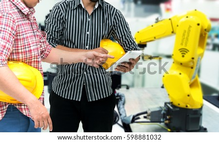 Industry 4.0 internet of things concept. Two Engineers and finger point to tablet for monitoring blur automation wireless robot machine arm background in smart factory.