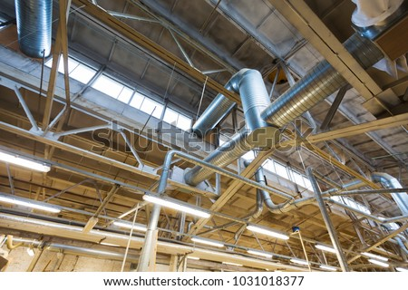 industry, manufacture and production concept - ventilation pipes system at factory shop