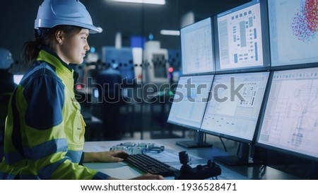 Industry 4.0 Modern Factory: Female Facility Operator Controls Workshop Production Line, Uses Computer with Screens Showing Complex UI of Machine Operation Processes, Controllers, Machinery Blueprints