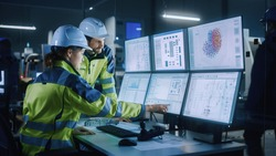 Industry 4.0 Modern Factory: Project Engineer Talks to Female Operator who Controls Facility Production Line, Uses Computer with Screens Showing AI, Machine Learning Enhanced Assembly Process