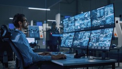 Industry 4.0 Modern Factory: Security Operator Controls Proper Functioning of Workshop Production Line, Uses Computer with Screens Showing Surveillance Camera Feed. High-Tech Security