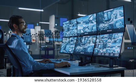 Industry 4.0 Modern Factory: Security Operator Controls Proper Functioning of Workshop Production Line, Uses Computer with Screens Showing Surveillance Camera Feed. High-Tech Security Сток-фото ©