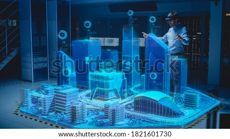 Industry 4.0: Modern Professional Architect Wearing Virtual Reality Headset Uses Gestures to Design, Manipulate Buildings for 3D City. Mixed Augmented Reality Software. VFX Graphics Effect Foto d'archivio ©