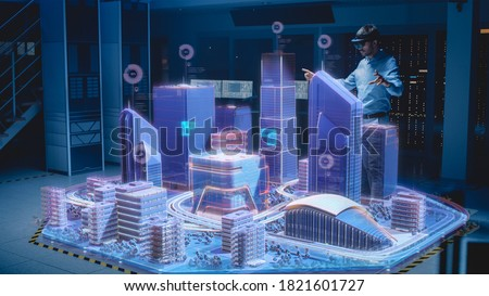 Industry 4.0: Modern Professional Architect Wearing Virtual Reality Headset Uses Gestures to Move, Design, Manipulate Buildings for 3D City. Mixed Augmented Reality Software. VFX Special Visual Effect ストックフォト ©