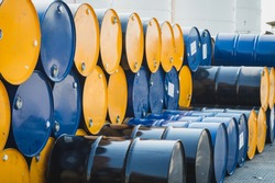 Industry oil barrels or chemical drums stacked up.chemical tank.container of  barrels of hydrocarbons.hazardous waste of black and blue tank oil.At the industrial event is a warehouse of barrels